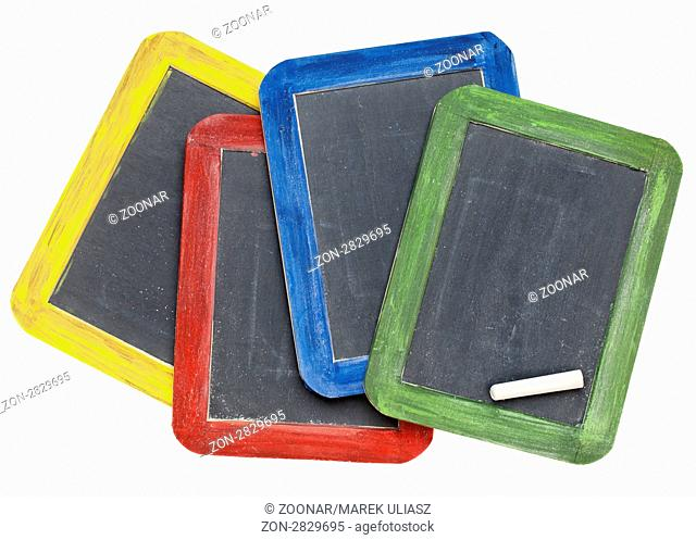 four blank vintage slate blackboards in colorful wood frames with chalk, isolated on white