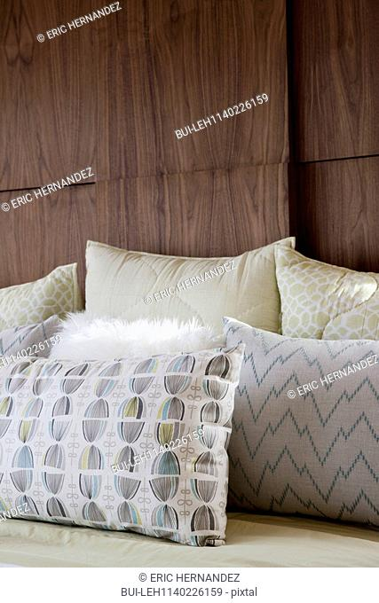 Close-up of pillows on bed against wooden wall at home