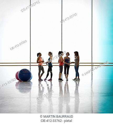 Women talking and drinking water at barre in exercise class gym studio