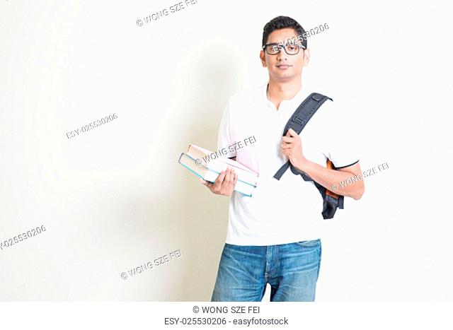 Portrait of Indian college student with books and backpack. Asian man standing on plain background with shadow and copy space
