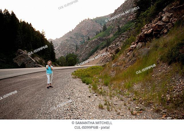 Woman taking photograph in Big Cottonwood Canyon, Salt Lake County, Utah, USA