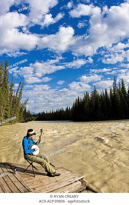 Female kayaker takes a break from paddling to play her banjo along the Athabasca River, Jasper National Park, Alberta, Canada