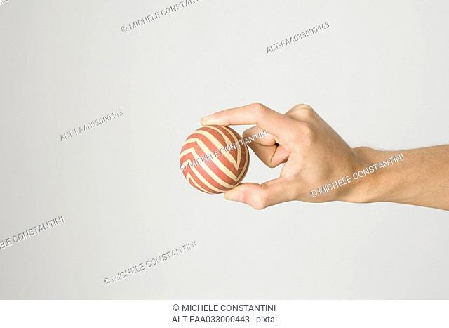 Hand holding striped ball