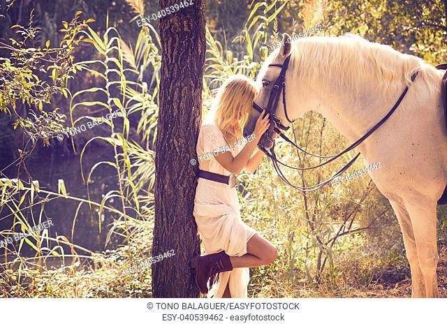 Blond girl hug her white horse in a magic light forest near river