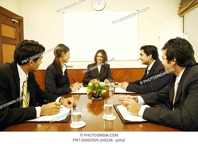 Five business executives at a meeting in a conference room