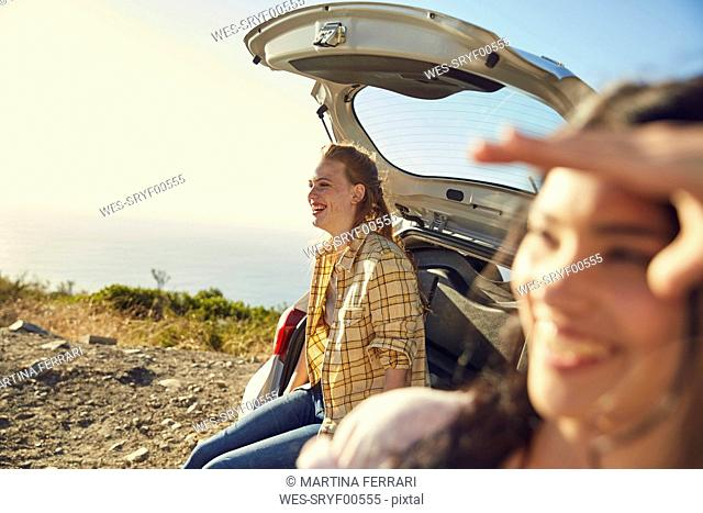South Africa, Cape Town, Signal Hill, two happy young women at a car at the coast