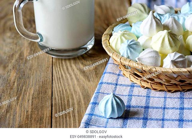 Meringues in a plate and with a cup of milk on a wooden table. Rustic style