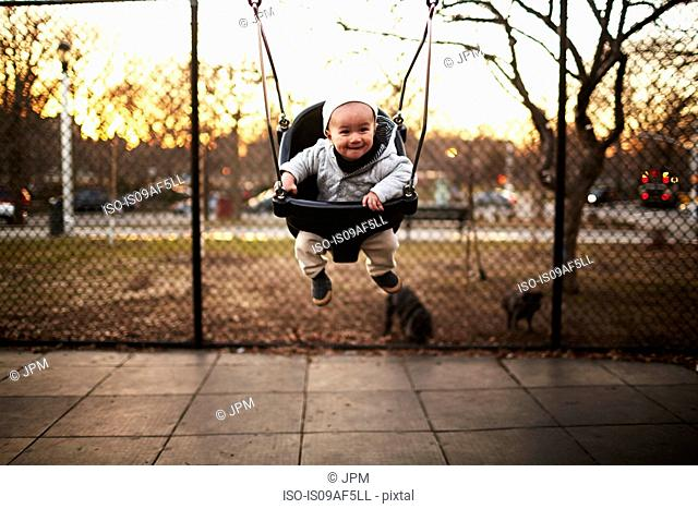 Baby boy sitting on swing in park