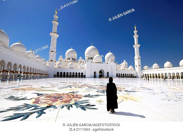 Woman wearing an abaya in the mosque courtyard. United Arab Emirates, UAE, Abu Dhabi, Sheikh Zayed Grand Mosque