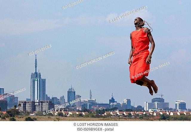Masai warrior jumping in mid air during traditional dance, Nairobi, Kenya, Africa