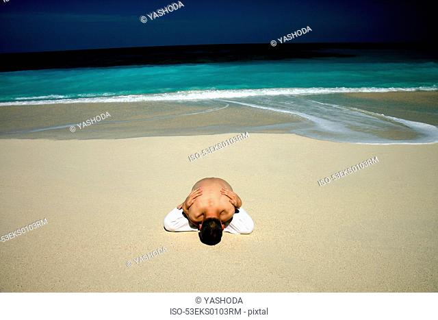 Man practicing yoga on tropical beach