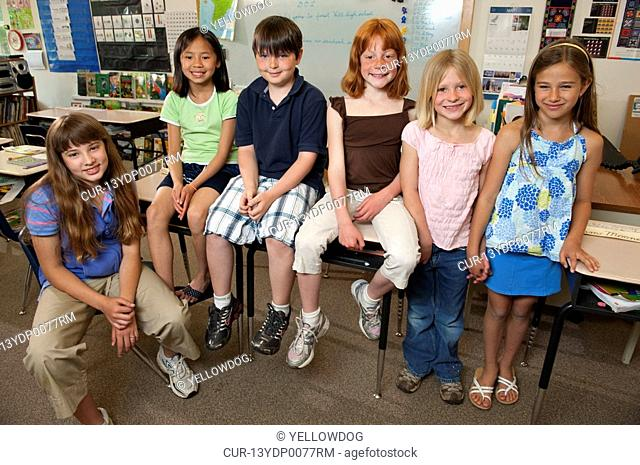 friends casually sitting on desks in classroom for group picture