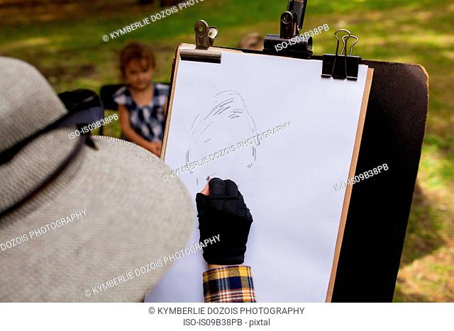 Woman sketching portrait of little girl in background