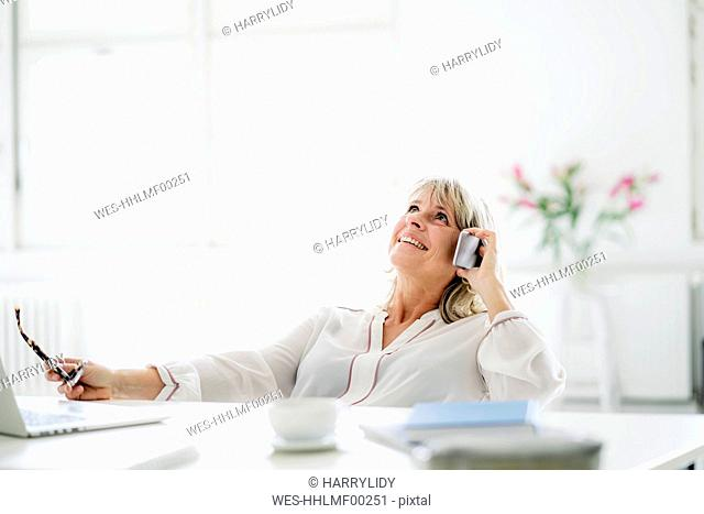 Happy mature businesswoman on cell phone at desk