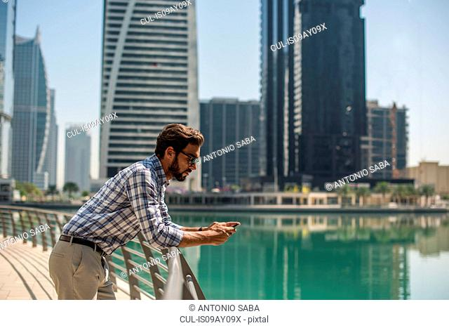 Young man leaning against waterfront railings reading smartphone texts, Dubai, United Arab Emirates