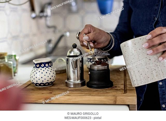 Woman preparing coffee in kitchen