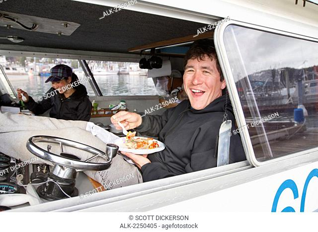 A Young Commercial Fishing Couple Enjoying Their Dinner And A Moment Of Relaxation Aboard Their Bowpicker; Cordova Alaska United States Of America