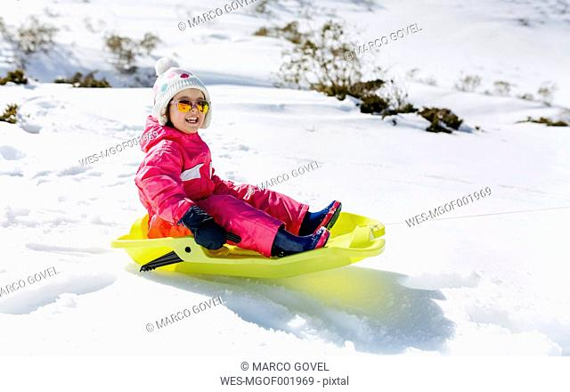 Spain, Asturias, girl with sledge in the snow