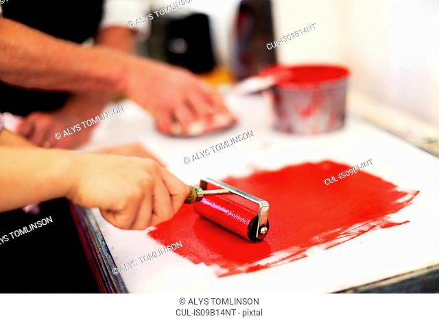 Close-up of hands using ink roller for letterpress printing in book arts workshop