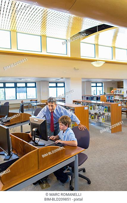 Teacher and student working at computer in library
