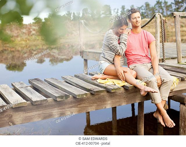 Serene couple siting on dock over lake