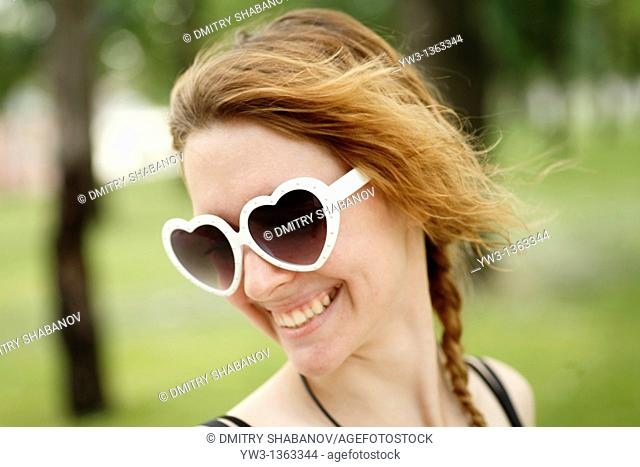 Portrait of young woman outdoors with heart-shaped sunglasses