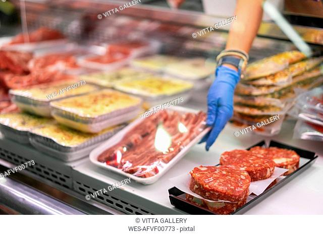 Woman in market stall putting packed meat on display