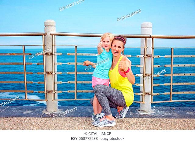 Look Good, Feel great! Happy mother and child in fitness outfit on embankment showing thumbs up