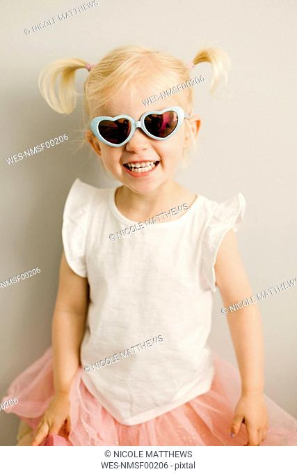 Portrait of blond little girl wearing heart-shaped sunglasses