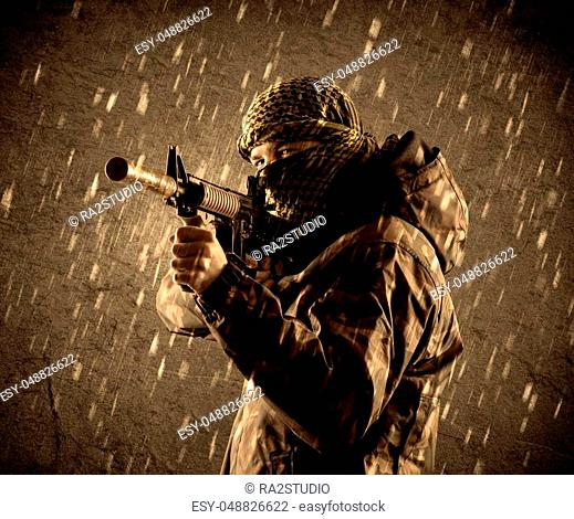 Portrait of dangerous heavily armed terrorist soldier with mask on grungy rainy background