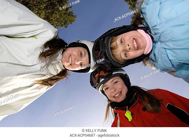 Three sisters take a break from skiing at Sun Peaks Ski Resort near Kamloops, British Columbia, Canada