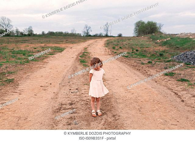 Portrait of shy girl standing on rural dirt track