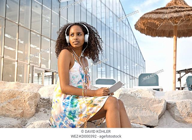 Young woman with headphones and digital tablet outdoors