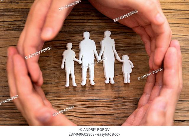 Elevated View Of Couple's Hand Protecting Family Figures Over Wooden Desk
