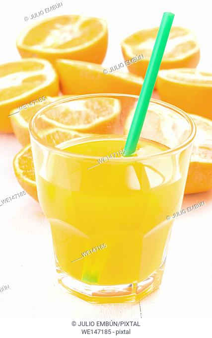 glass of juice and cut oranges on white table