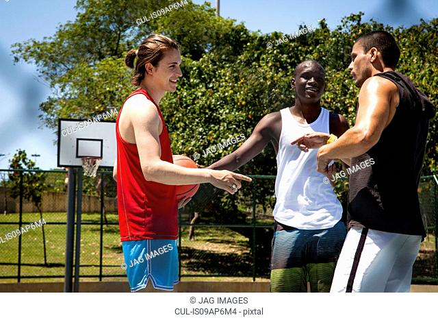 Male basketball players team talking on basketball court
