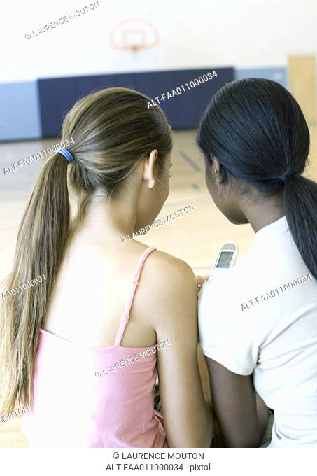 Two teen girls sitting close together in school gym, looking at cell phone