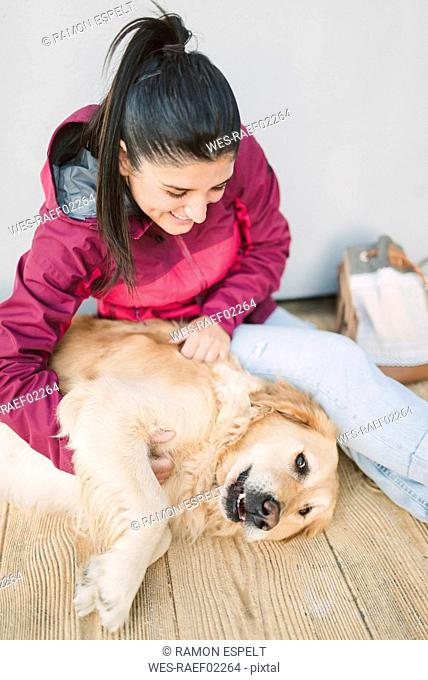 Happy young woman stroking and playing with her golden retriever dog