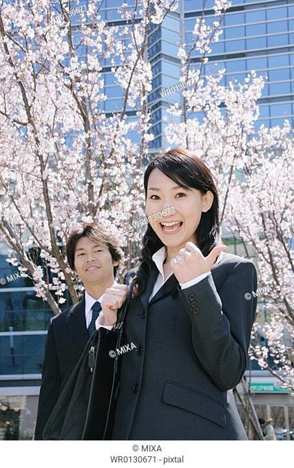 Young woman and mid adult man standing in front of cherry blossoms