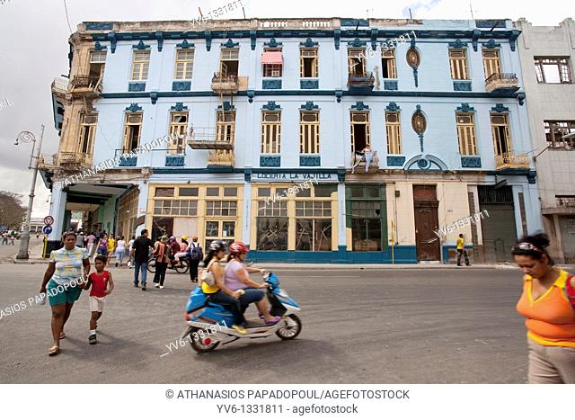 Typical Central Havanas Road With Scooters And People Crossing The Street While An Ex Luxurious Blue Building Is Noticeable At The Background, Centro Habana