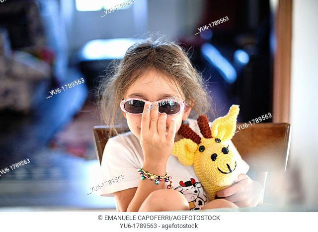 Little girl plays with glasses sitting at the kitchen table