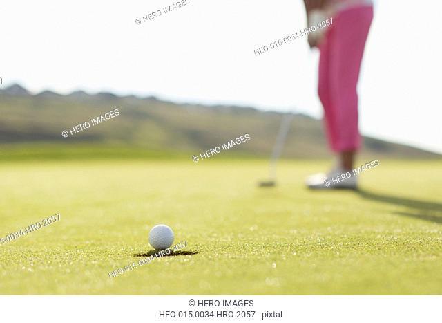 close-up of golf ball at golf hole