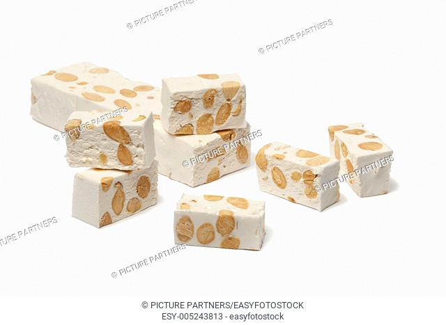 Pieces of Nougat with almonds and pistachio nuts on white background