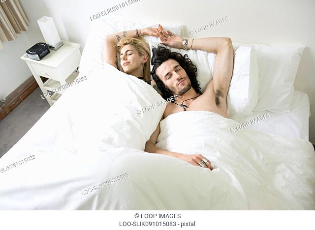 A cool young couple relaxing in bed with their eyes shut