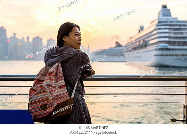 A young woman at the waterfront with cruise ships in the harbour in the background, Kowloon; Hong Kong, China