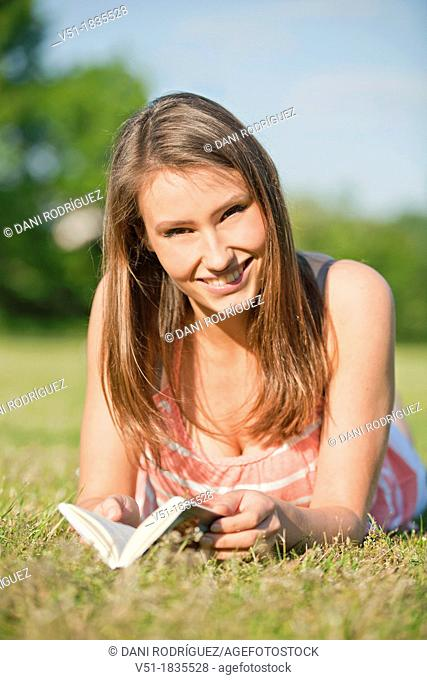 Pretty young woman reading a book in park and smiling at camera