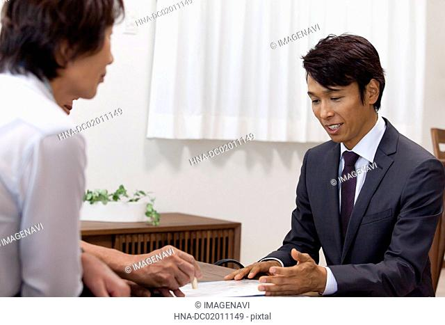Old couple putting a chop on a contract document