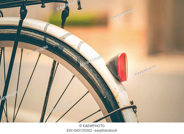 The red reflectors on the back of the vintage bicycle are used as illustrations for the text and used as backgrounds, presented in vintage tone patterns
