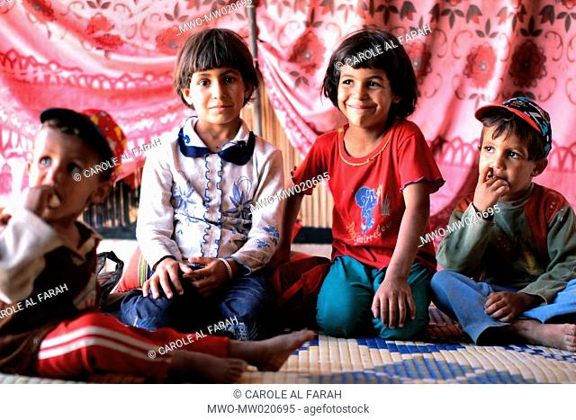 Portraits of Abu Mohammad's four children Malek, 9, Nour, 6, Mohammad, 4, and Adnan, 2, are sitting in the tent where they live with their parents Sahnaya