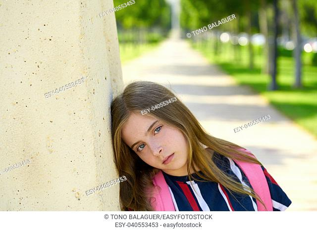 Blond kid student girl sand bored face gesture in the park